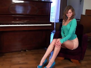 Cute darling with a shaved pussy enjoys masturbating on a piano